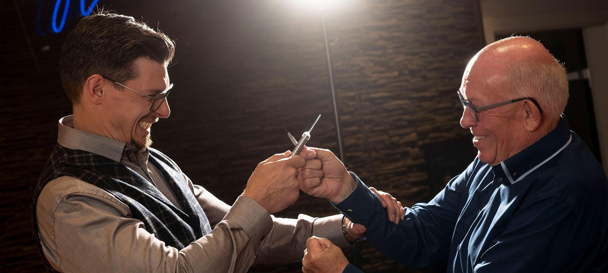 Zwei Personen die sich lachend aus Spaß mit Akustik- und/oder Optikwerkzeugen duellieren