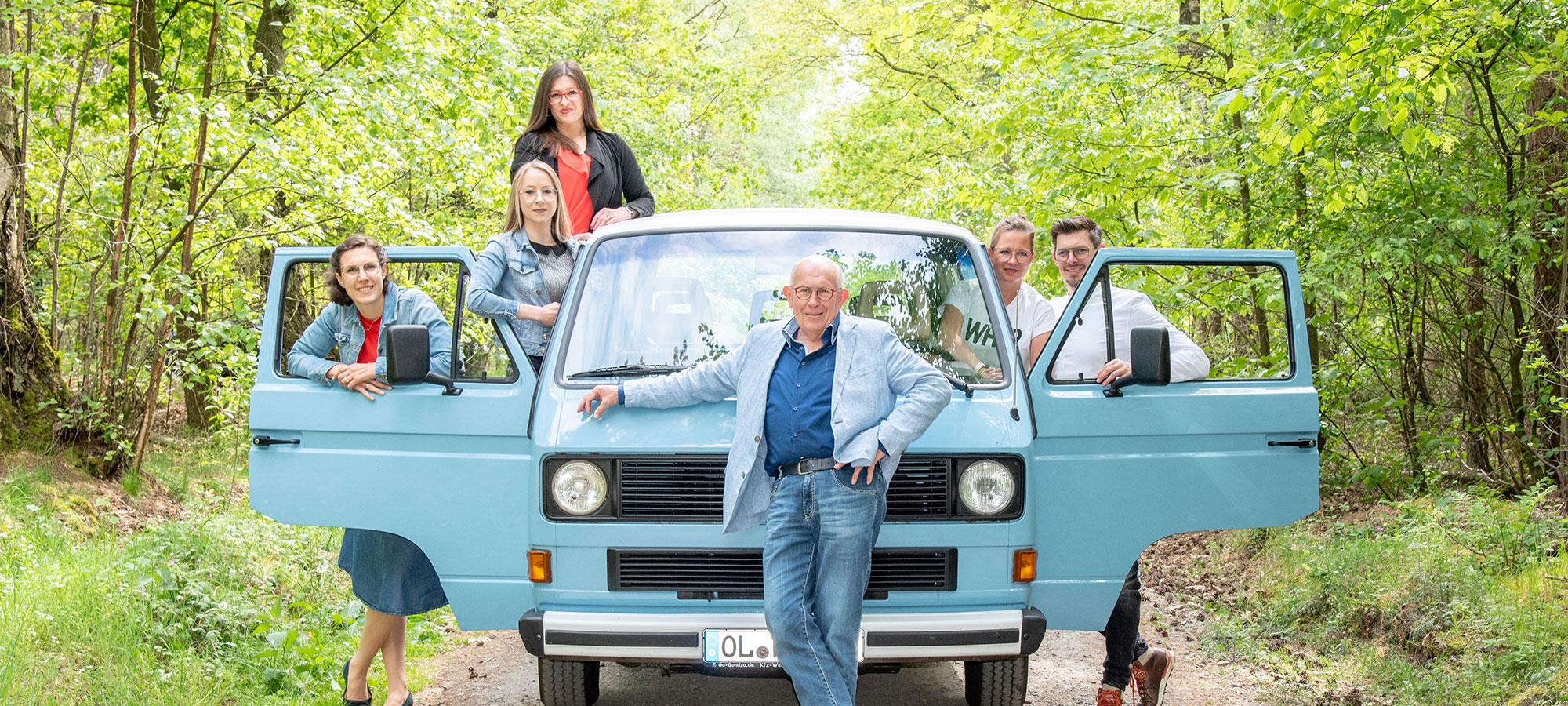 Gruppenfoto vom Harting Team mit einem blauen Van